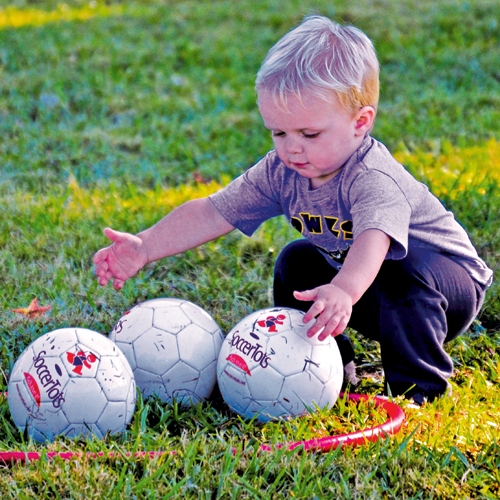 Young Child playing with three soccer balls